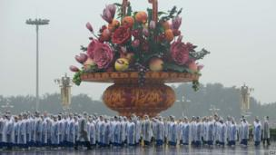 People queue up before a giant vase on Tiananmen Square prior to a wreath-laying ceremony marking the 64th anniversary of founding of the People's Republic of China by Mao Zedong, in Beijing on 1 October, 2013.