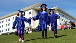 Children wearing UEA graduation gowns and caps