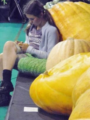 Girl sitting by big pumpkin