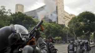 Riot squad officers shoot tear gas during a protest in Rio de Janeiro, Brazil