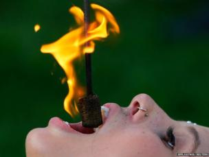 Kristin Decker, a street performer, eats fire