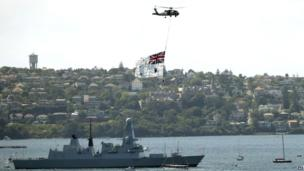 A Royal Australian Navy helicopter towing the Australian naval ensign passes over HMS Darling in Sydney