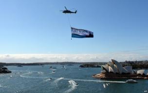A Royal Australian Navy Seahawk helicopter flies the International Fleet Review flag over the Sydney Opera HouseNew