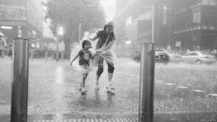 Woman and child walking through torrential rain in Singapore