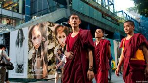 Monks walking along Singapore's Orchard Road, a shopping haven.