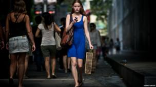 An off-duty model walks along the road studying her mobile phone.