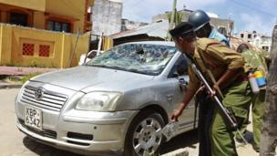 Kenyan policemen check on a car damaged by youths protesting after Friday Muslim prayers in Mombasa, Kenya - Friday 4 October 2013