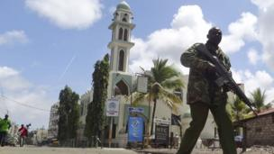 An armed Kenyan policeman patrols past the Masjid Musa Mosque in Mombasa, Kenya - Friday 4 October 2013