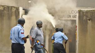 An armed policeman carrying a pistol and tear gas patrols while firemen attempt to put out a fire in the Salvation Army Church after it was set on fire by rioting youths, Mombasa, Kenya - 4 October 2013
