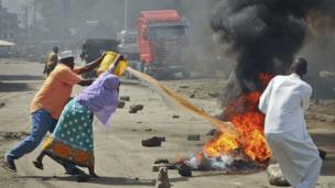 Residents in the Kenyan city of Mombasa throw water to put out the flames from burning tyres set on fire in a street by rioting youths - Friday 4 October 2013