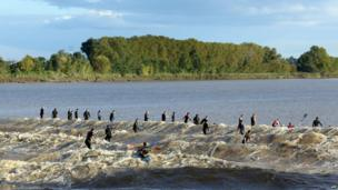 "People surf the ""Mascaret"", a tidal wave on the Dordogne river, at Saint-Pardon-de-Vayres, south-western France (6 October 2013)"