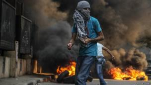 Protester clashes with the police as smoke rises