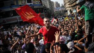 A man sits on the shoulder of another protester while chanting against the military-backed government