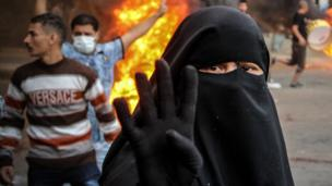 A supporter of Mr Morsi raises her hands with four raised fingers - a symbol for the Rabaah al-Adawiya mosque where hundreds of Muslim Brotherhood supporters were killed by security forces.