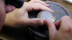 Chief engraver Gordon Summers looks at a cast for the new coin