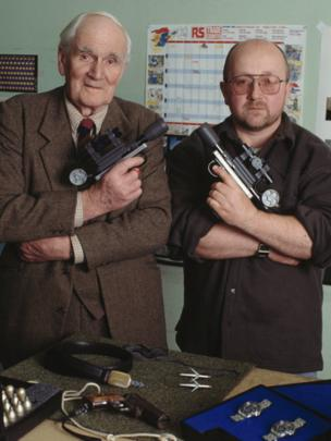 Desmond Llewelyn with special effects technician Nicholas Finlayson, and some of the props from the James Bond film GoldenEye, 1995