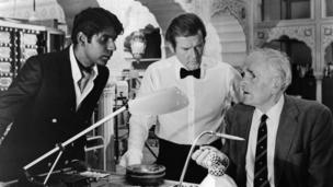 Vijay Amritraj and Roger Moore looking at new gadget that Desmond Llewelyn has created in a scene from the film 'Octopussy', 1983.