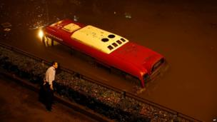 A man looks at a submerged bus in a flooded underpass in Shanghai, China