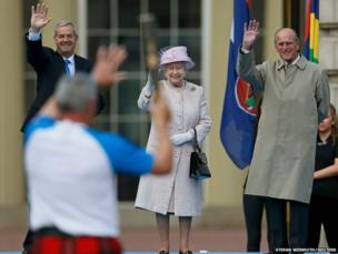 Alan Wells, the first baton bearer waves to Britain's Queen Elizabeth, Prince Philip (right) and Robert Smith, chair of Glasgow 2014, at Buckingham Palace in London