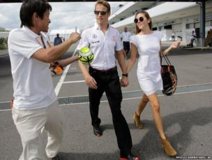Formula 1 McLaren driver Jenson Button with his girlfriend Jessica Michibata walk down the paddock as a fan asks for his autograph