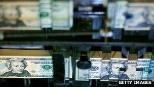 Twenty dollar bills roll through a government printing press.