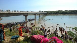 Indian Hindu pilgrims bathe in the Sindh river alongside the bridge.