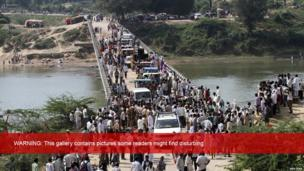 People cross a bridge after a stampede near Ratangarh temple in Datia district