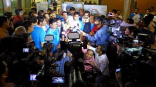 The Queen's Baton arrives amid a media scrum in New Delhi.