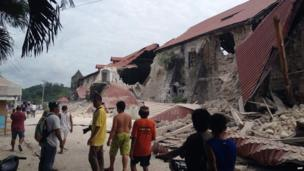 People walk past the damaged Church of San Pedro in the town Loboc, Bohol