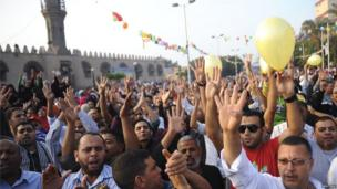 Anti-government protestors gesture and shout anti-military slogans outside a mosque in Cairo.