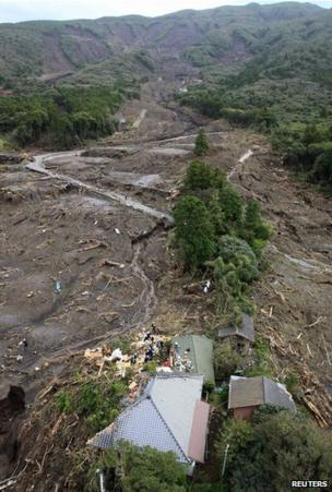 Rescue workers searching among collapsed houses following a landslide caused by Typhoon Wipha on Izu Oshima island, south of Tokyo