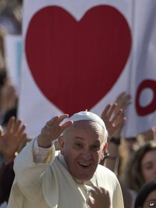 Pope Francis salutes the faithful as he arrives for his weekly General Audience in St. Peter Square
