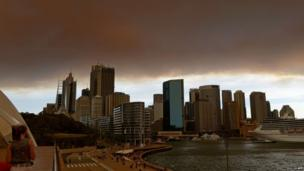 Smoke and ash from wildfires burning across the state of New South Wales blankets the Sydney city skyline