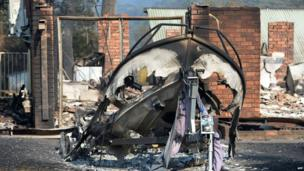 A burnt-out boat (C) sits in front of a house destroyed by bushfires in Winmalee in Sydney's Blue Mountains on 18 October 2013