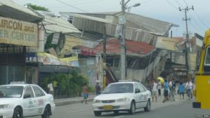 House that has collapsed on a busy street as a result of the earthquake. Photo: Patrick Tieng