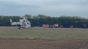 Helicopter, recovery vehicles and rescue workers in a field after light aircraft crash. Photo: Laurant Matthieu