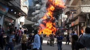 Residents move away from a fire at a fuel and oil shop in Aleppo