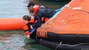 Trainees lift a patient into a rubber lift raft