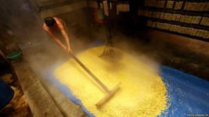Alim Silalahi dries boiled soy beans