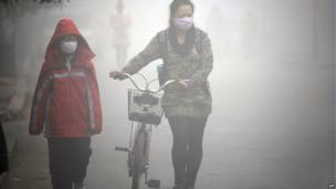 A woman walks with her child on a street as schools were closed due to the heavy smog in Jilin, northeast China's Jilin province on 22 October 2013