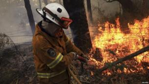 Rural Fire Service firefighter sprays water on to a fire burning a home in the Blue Mountains suburb of Faulconbridge. 22 Oct 2013