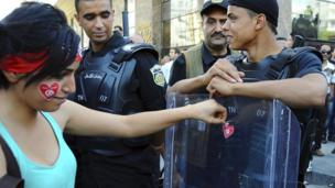 A woman with a heart-shaped sticker on her face adds another stick to a police officer's shield during a protest in Tunis, Tunisia - Wednesday 23 October 2013