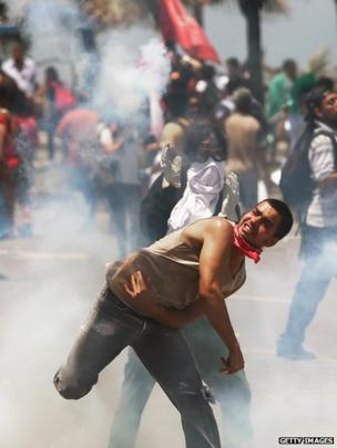 A protester throws a tear gas canister back towards police outside the seafront Windsor Barra hotel on October 21, 2013