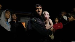Sashka Ruseva holds her son Atanas, as she speaks to media outside her house in the town of Nikolaevo.