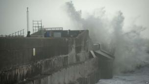 Large waves crash against the walls of Brighton Marina