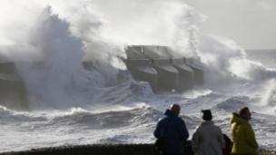 People watch the waves batter into the sea wall of a marina in Brighton,