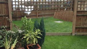 A broken garden fence. A missing panel has flown into the neighbour's garden.