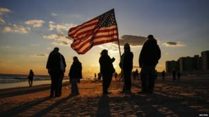 People stand with an American flag during a remembrance ceremony along the beachfront damaged by hurricane Sandy on 27 October 2012 in the Rockaways section of the borough of Queens in New York.