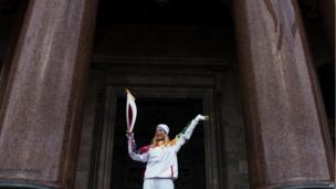 Torchbearer for winter Olympics posing in front of Cathedral in St Petersburg.