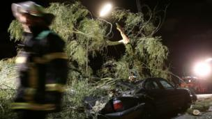 A A fire fighter passes by a car hit by a tree in Hamburg, northern Germany (28 October 2013)